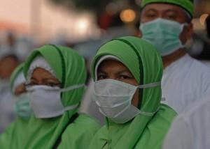 Sejumlah calon haji asal  Indonesia memakai  masker ketika melintas  dikawasan perdagangan di Misfalah, Makkah,