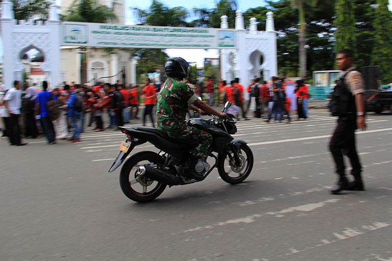 Pengendara melewati para aktivis yang sedang menggelar aksi Hari Anti Korupsi Internasional (HAKI) di depan Masjid Raya Baiturrahman, Banda Aceh. (Foto SeputarAceh.com/M Iqbal)