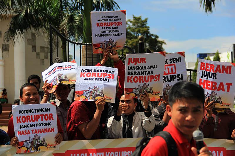 "Para aktivis membawa slogan ""Uleue Beumate Ranteng Bek Patah Koruptor ta Peugleh Jeut Teudong Nanggroe Syari'at"" di Hari Anti Korupsi Internasional (HAKI) di depan Masjid Raya Baiturrahman, Banda Aceh. (Foto M Iqbal/SeputarAceh.com)"